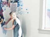 Прекрасная девушка наносит рисунок на подготовленные под покраску стены