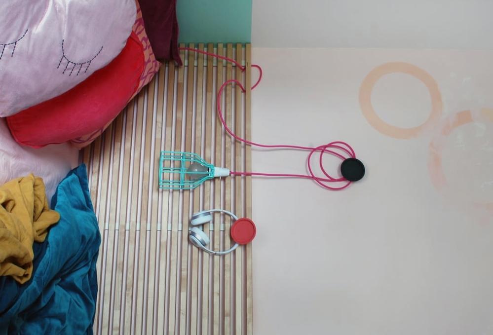 Необычный светильник с наушники украшают эту миниатюрную спальню