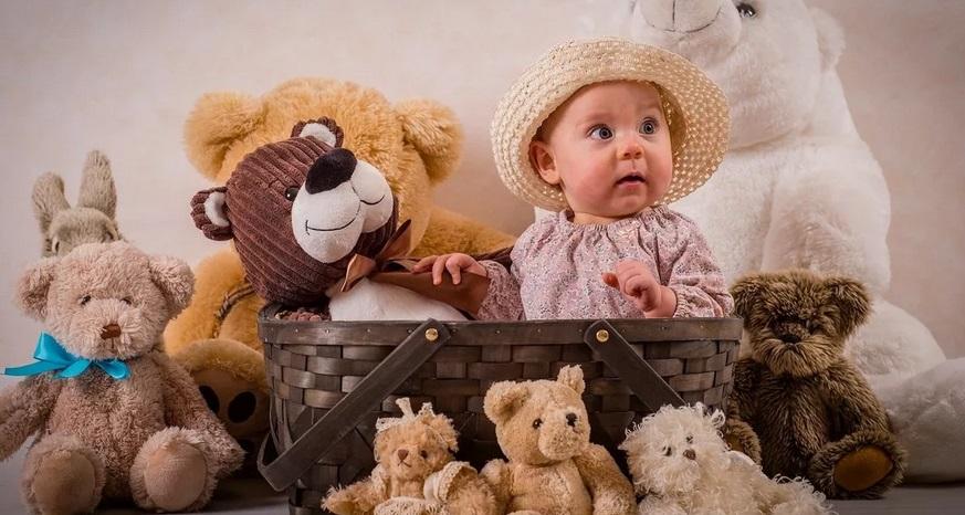 Ребенок в куче плюшевых игрушек