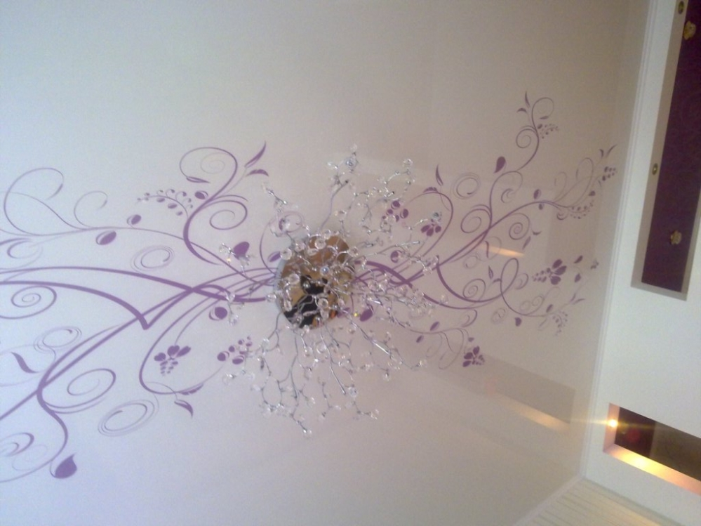 Натяжной потолок с ярким орнаментом фиолетового цвета перекликается с люстрой и создает необычный эффект